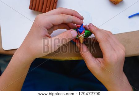The child is engaged in modeling of plasticine sitting in the children's table with blanks and toys from plasticine. Educational and interesting activities for children. Top view.