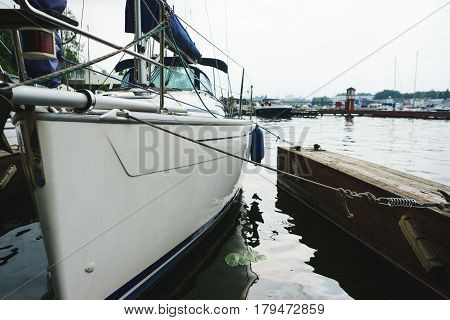 Large white sailing boat moored to a pier during a stop at the docks. Walk on a yacht on a cloudy day. Leisure at sea.