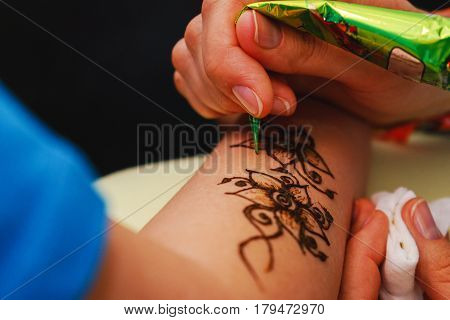 The process of applying to the skin ornament painted with henna. Hand master drawings on the body.