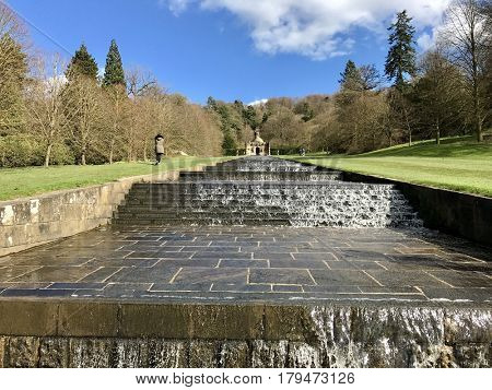 CHATSWORTH HOUSE - MARCH 31, 2017: The Cascade water feature and Cascade House in the gardens of Chatsworth House in the Derbyshire Dales, Peak District, Derbyshire, UK.