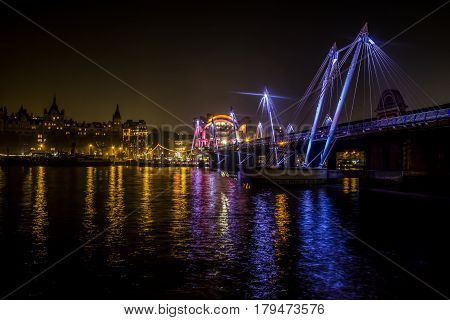 Hungerford Bridge and Golden Jubilee Bridges  and Whitehall Gardens at night with lights reflected in Thames water , London