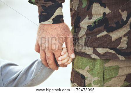 Two Hands  Of One Family - Father And Child Together. The Concept Of Family Unity Protection Support