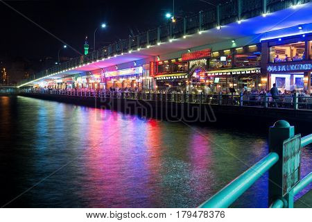 ISTANBUL - MAY 25, 2013: Tourists relax in the restaurants located on the first level of the famous Galata Bridge at night. The Galata Bridge is one of the main attractions of Istanbul.