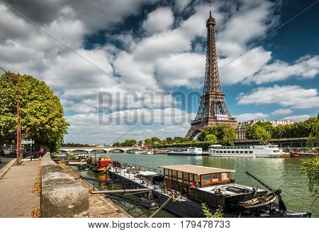 The River Seine with boats and Eiffel tower in Paris. Residential barges on the foreground.