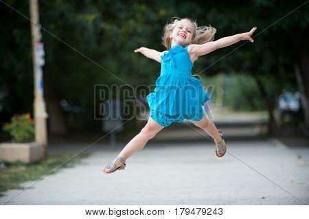 small baby girl or cute happy child with adorable smiling face and bow in blonde hair in blue dress jumping in summer outdoor on blurred background