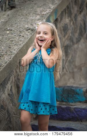 Small Baby Girl With Surprised Face In Blue Dress Outdoor