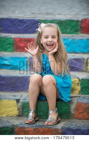 Small Happy Baby Girl In Blue Dress On Colorful Stairs