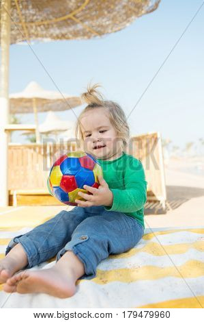 small baby boy or cute child with happy face and blonde hair in green shirt and pants sitting barefoot playing with colorful ball at sunny summer outdoor beach on natural sky background
