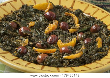 Traditional Moroccan dish with spinach, olives and preserved lemon close up