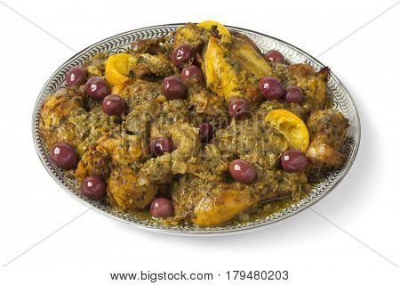 Moroccan dish with chicken, preserved lemon and purple olives on white background