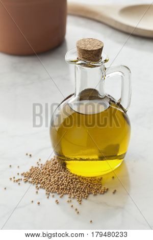Glass bottle with mustard oil and a heap of seeds