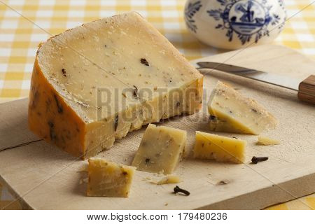 Piece of aged Dutch cheese with cloves on a cuttingboard for dessert