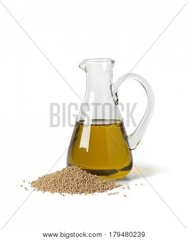 Glass bottle with mustard oil and a heap of seeds on white background