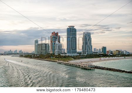 South Miami Beach. Miami skyscrapers with blue cloudy skywhite boat sailing next to Miami downtown Aerial view