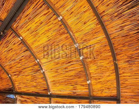 Close up of internal structure of outdoor sun shade umbrella with metal beams and rings and wooden sticks.