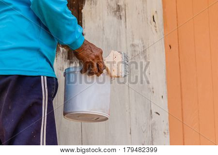 Painters are painting wooden houses in construction.