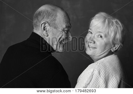 Black and white studio shot of aging couple having fun and blessed with love. During love dancing man is looking at his partner and she is smiling to the camera. Love and family concept.