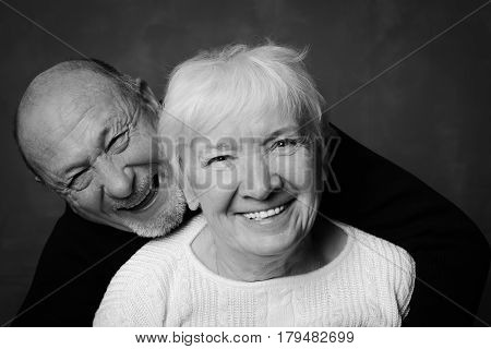 Black and white studio shot of handsome senior couple on a dark background. Man in black hugs his wife in white smiling and laughting looking at the camera. Love and devotion concept