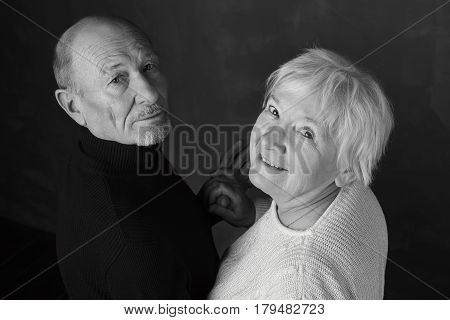 Black and white portrait of elegant senior couple. Man and his wife are dancing indoors on dark grey lbackground ooking deeply to the camera hand by hand. Love and family concept