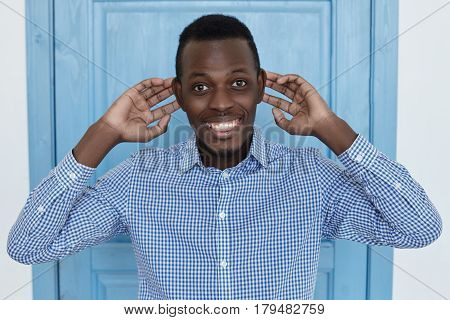 Headshot of bug-eyed young African man grimacing looking at camera with funny face expression clowning and having fun indoors pulls his ears fooling around and indulge.