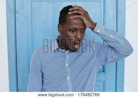 Studio shot of shocked and desperate dark-skinned man wearing blue shirt holding hand on head looking down and screaming with scared expression and mouth wide open because of some terrible mistake