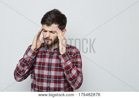 Portrait of attractive young man with beard holding her head suffering from pain. Migraine and headache. Overworked stressed and have business problems.
