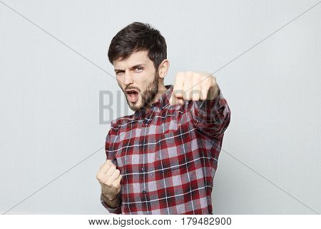 Studio shot of excited young bearded man dressed in casual shirt demostrating his power and superiority. Celebrating success with tight fists and opened mouth looking at the camera.