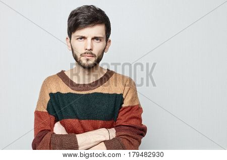Sudio shot of young brunette attractive guy gazing at the camera with suspicion. Caucasian man in vintage sweater crosses his hands and staring forward.