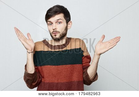 Studio shot of young bearded Causasian man in old fashioned colorful sweater spreads his hands in amazement to the sides. In surprise he looks forward. Human emotional concept.