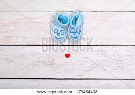 Blue booties for the boy and a small red heart on a white wooden background. view from above