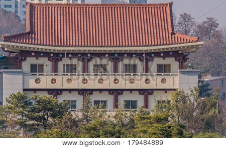 Daejeon South Korea March 13 2017: Building with classical oriental styling with red clay tiled roof metal mesh windows and intricate designs in the wall of the portico