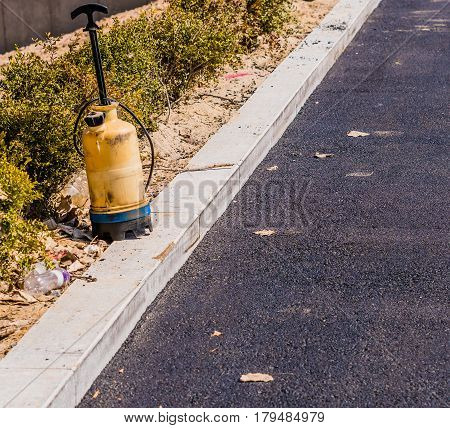 Plastic industrial spray bottle sitting on the curb of parking lot with black asphalt paving and a row of green bushes