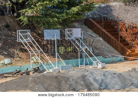 Three movable basketball nets at construction site under large pine tree beside set of wooden stairs with large pile of loose dirt in the foreground