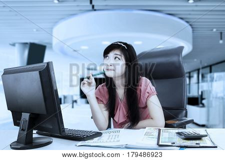Picture of beautiful business woman looking sideways while working with a computer and sitting in the office