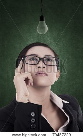 Business woman is looking at unlit light bulb representing that she hasn't found a bright idea yet