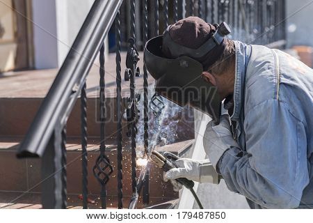 A worker welding metal handrails on the stairs. Wrought iron railings. Private house. Ukraine.