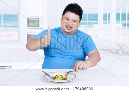 Photo of overweight person smiling at the camera while showing thumb up and enjoy salad at home