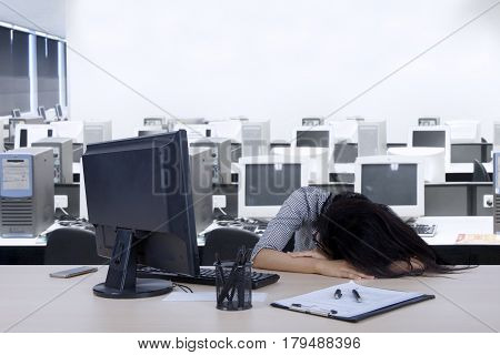Image of Asian female worker is sleeping in the workplace with a computer and clipboard on the desk