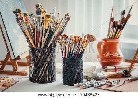 Artistic Equipment: Easel,  Paintbrushes, Tubes Of Paint, Palette And Paintings On Work Table In A A