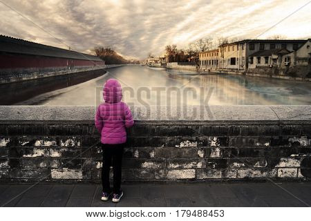 Little girl wearing a pink jacket and standing on a stone bridge while looking at the river in the Forbidden City at Beijing China