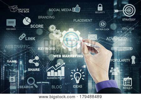 Male entrepreneur hand using a stylus pen to press a SEO button on the virtual screen. SEO concept