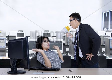 Picture of young leader reprimanding his employee with a megaphone while standing in the office