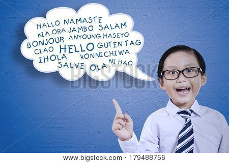 Portrait of cute little student learns multilingual while standing with a cloud bubble