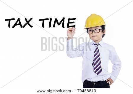 Cute little businessman with helmet writes tax time on whiteboard isolated over white