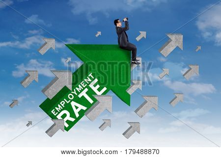 Image of male job hunter using binoculars while sitting on the upward arrow sign with employment rate text