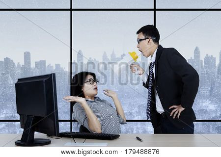 Picture of young male manager looks angry while shouting at his secretary through megaphone in the office