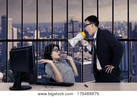 Portrait of a young male manager reprimanding his subordinate with a megaphone while standing near the window