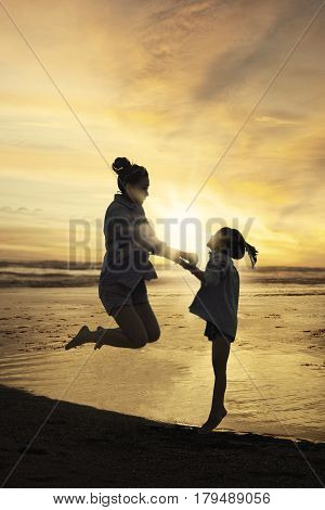 Silhouette of happy mother and her daughter leaping at shore while holding hands together shot at sunset time