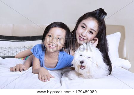 Image of young beautiful mother and her daughter embracing their puppy while lying on the bedroom