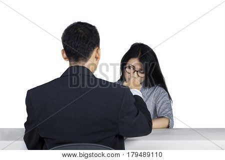 Young woman looking down in a job interview and looks nervous while the recruiter pointing her